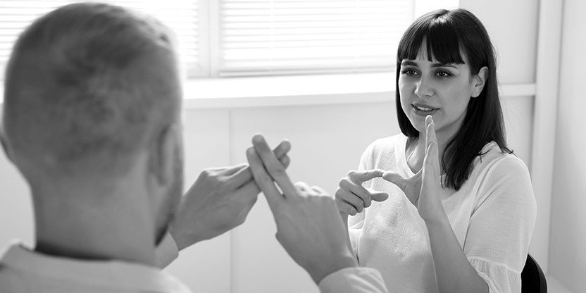 Image shows a man and a woman in an office communicating using sign language.