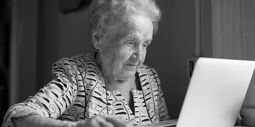 Image shows an elderly lady in her home looking at a laptop screen.