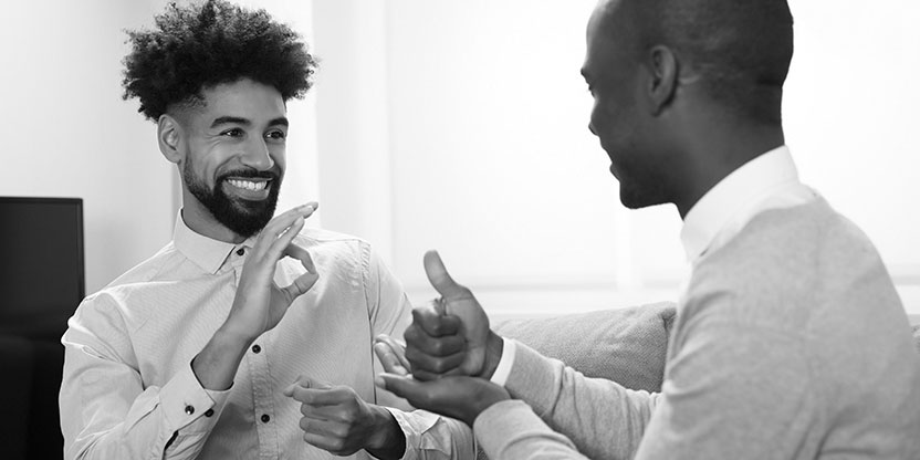 Two young men in an office communicating using sign language.