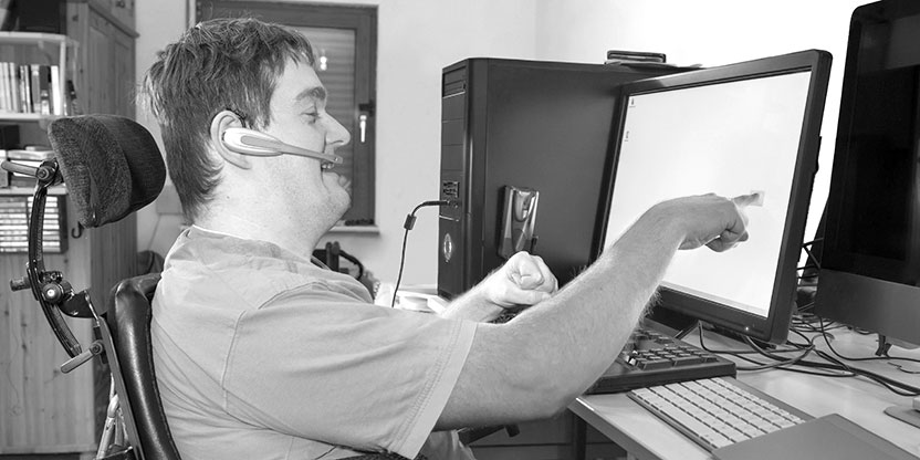 A man with a cognitive and mobility impairment smiles as he uses a touchscreen monitor on his PC.