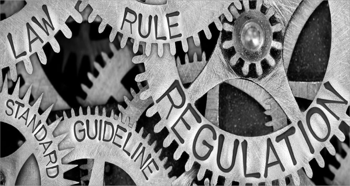 Cogs with words imprinted on them. Words shown are law, standard, rule, guideline and regulation.