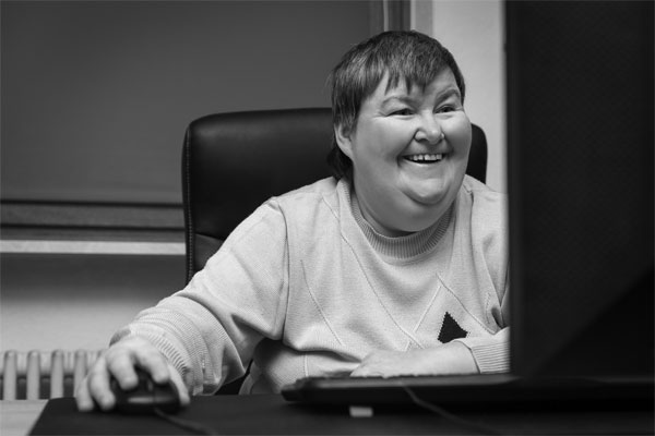 A woman with a cognitive impairment smiles as she carries out some online learning on her pc.